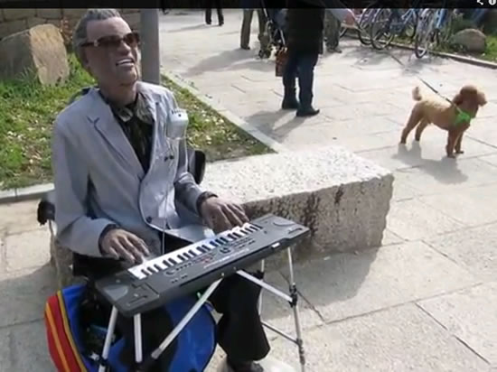 Animatronic Ray Charles robot.webp  Japanese robot sings Southern All Stars hit Ellie My Love sitting on a bench in Osaka